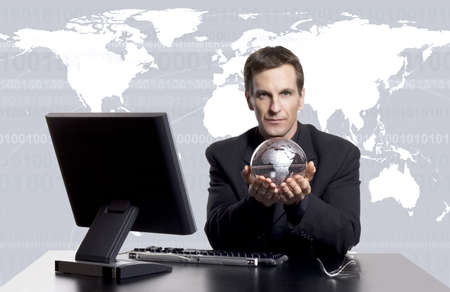 Businessman at his desk holding a globe with world map in the background