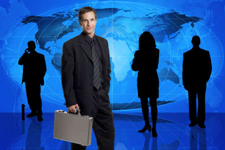teleconference: Businessman with briefcase standing in front of an earth map and other business people in silhouette Stock Photo
