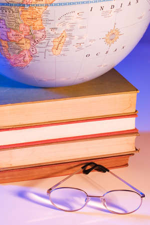 higher intelligence: Globe on stack of books with glasses Stock Photo