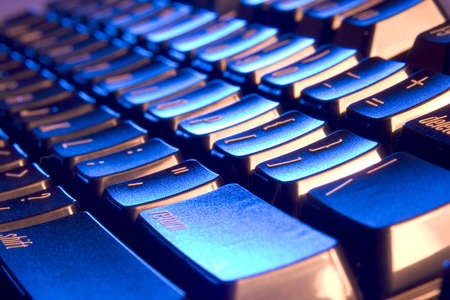 Macro of a computer's keyboard with blue and orange lighting