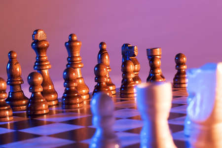 calculated: Chessboard and Chess pieces photographed with blue and orange lighting.