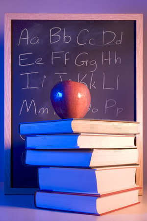 instruct: Apple on books in front of a chalkboard with the alphabet written on it.