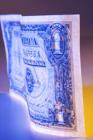 financials: A dollar photographed with orange and blue lighting. Stock Photo