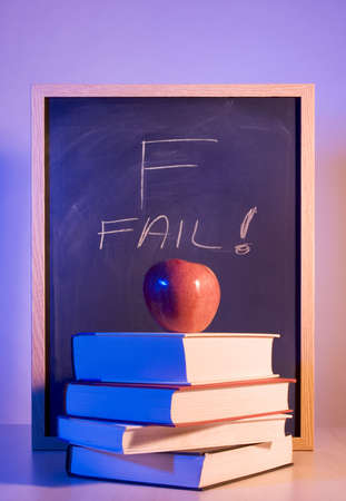 higher intelligence: A Stock Image of an Apple Placed on a Stack of Books in Front of a Chalkboard With Fail Written on it. Stock Photo