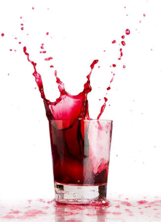 splash mixed: Ice cube dropped into a glass of grape juice  Stock Photo
