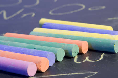 Close up of a row of chalk placed on a chalkboard that has the alphabet written on it. photo