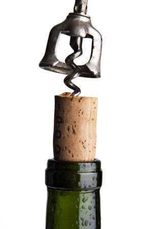 Close up of a corkscrew uncorking a bottle of red wine