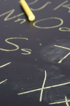 Piece of chalk placed on a chalkboard that has the alphabet written on it. photo