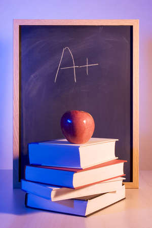 cramming: Apple on books in front of a chalkboard with A written on it