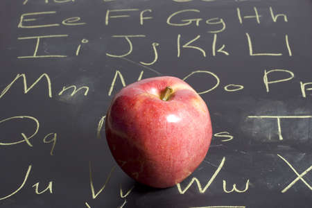 higher intelligence: Apple placed on a Chalkboard that has the alphabet written on it.