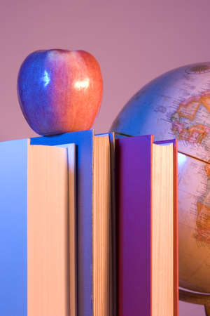 higher intelligence: Apple placed on a stack of books in front of an antique earth globe.