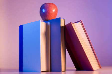 higher intelligence: Apple placed on a stack of books Stock Photo