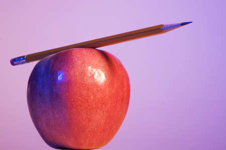 instruct: Pencil placed on top of an apple Stock Photo