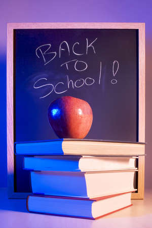 instruct: Apple Placed on a Stack of Books in Front of a Chalkboard With back to school written on it