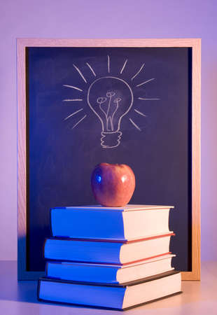 higher intelligence: Apple Placed on a Stack of Books in Front of a Chalkboard With a Light Bulb Drawn on it. Stock Photo