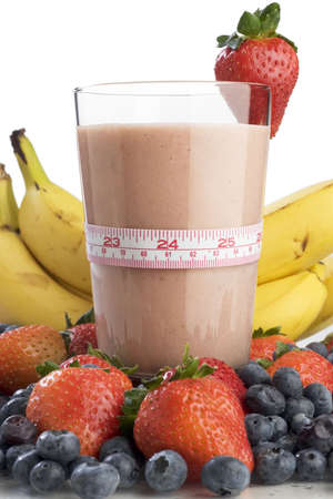 Smoothie surrounded by fruit and wrapped with a tape measure  Stock Photo