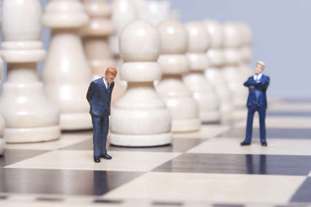 deliberate: Business figurines placed on chessboard with chess pieces