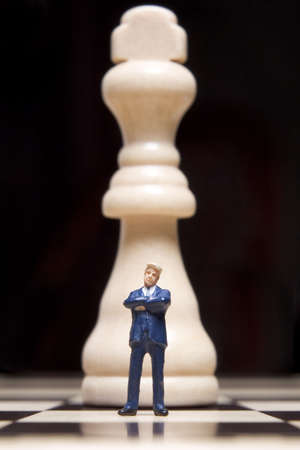 Business figurines placed on chessboard with chess pieces Banco de Imagens - 3591061