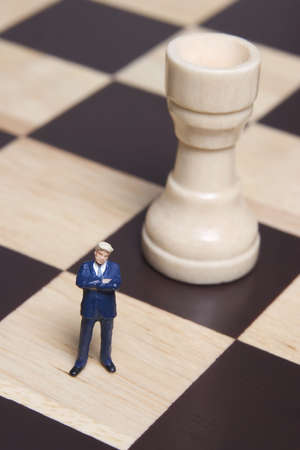 calculated: Business figurines placed on chessboard with chess pieces
