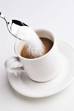 cuiller�e: Cuiller�e de sucre sur le point d'�tre agit� dans une tasse de caf� Banque d'images