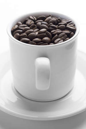 Coffee cup full of coffee beans on white  photo