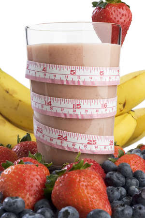 Smoothie surrounded by fruit and wrapped with a tape measure  Imagens