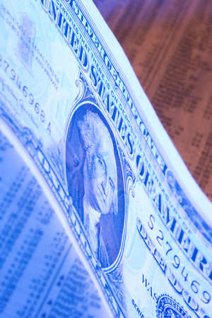 A dollar placed on a stock report photographed with orange and blue lighting.