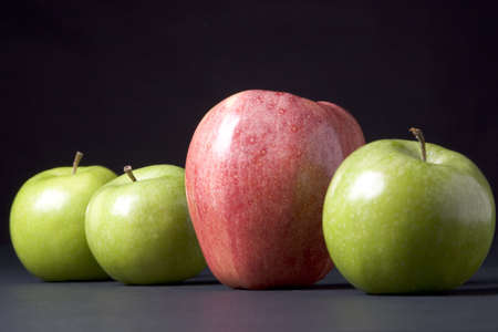 A big red apple next to small green apples