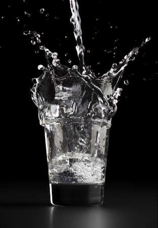 d�bord�: Couler un verre d'eau, les �claboussures d'eau sur le verre