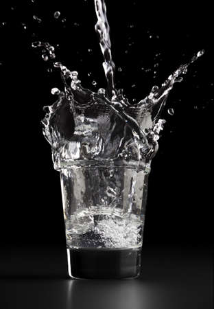 Pouring a glass of water, water splashing out of the glass