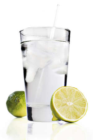 Glass of water on a reflective tabletop with limes