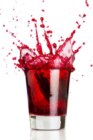 Ice cube dropped into a glass of grape juice  Foto de archivo