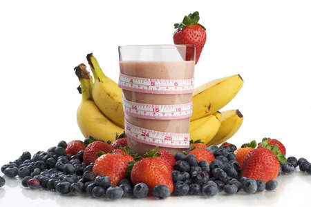 Smoothie surrounded by fruit and wrapped with a tape measure  Foto de archivo