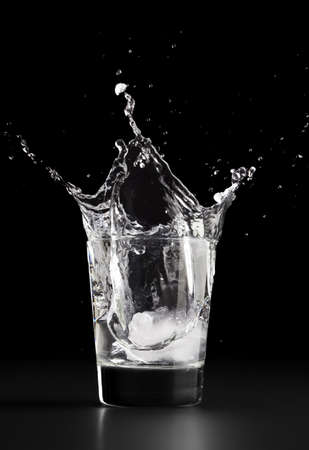 Water splash, dropping an ice cube into a glass of water Stock Photo