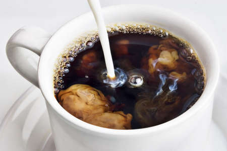 Pouring creamer into a cup of coffee Stock Photo