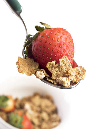 fortified: Spoon and bowl of breakfast cereal with strawberries Stock Photo