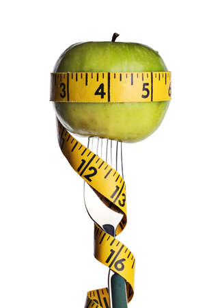 Apple on a fork wrapped with a tape measure