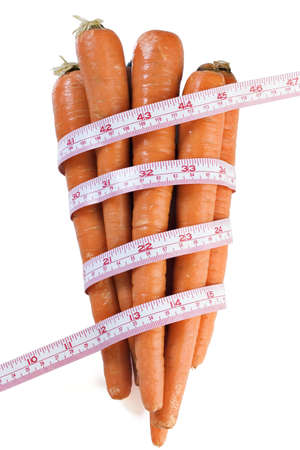 Carrots wrapped with a tape measure on white  Stock Photo - 4866420