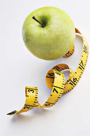 Apple with a tape measure on a reflective tabletop