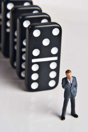 conspire: Business figurine and dominos  Stock Photo