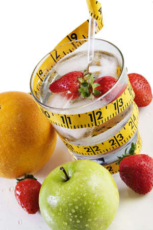Glass of water on a reflective tabletop with fruit and a tape measure