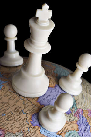 deliberate: Chess pieces on an earth globe