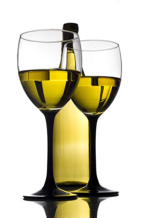 Glass and bottle of white wine on a reflective tabletop Foto de archivo