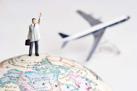 Business figurine on earth globe with toy airplane in background  Stock Photo