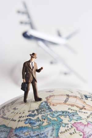 jetsetter: Business figurine on earth globe with toy airplane in background  Stock Photo