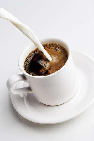 Gießen Sahne in eine Tasse Kaffee Standard-Bild