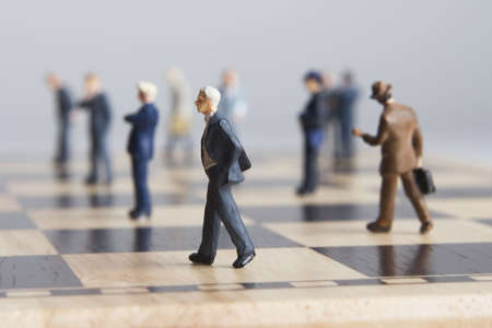 figurines: Business figurines placed on chessboard Stock Photo