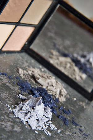 화강암 탁상 위에 놓인 분말 메이크업과 거울