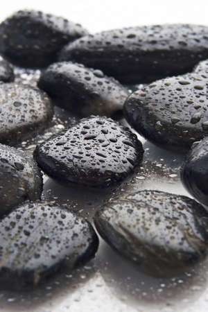 lastone therapy: Wet river rocks, Lastone therapy stones, on a white reflective tabletop,  Stock Photo