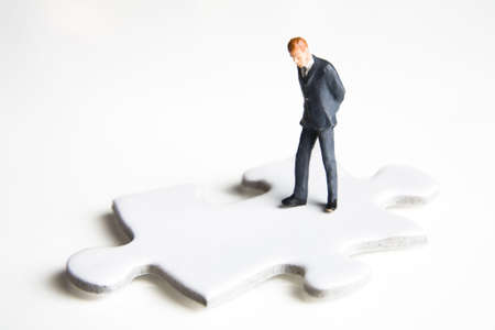 strategizing: Businessmen figurines standing on a puzzle piece